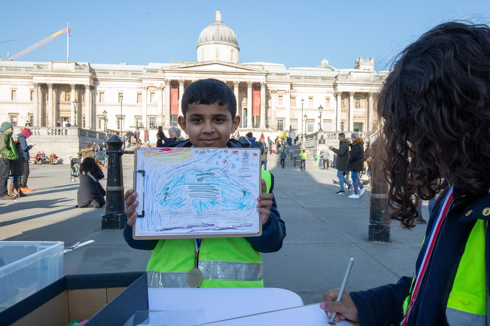 A young artist shows his colourful sketch in Trafalgar Square