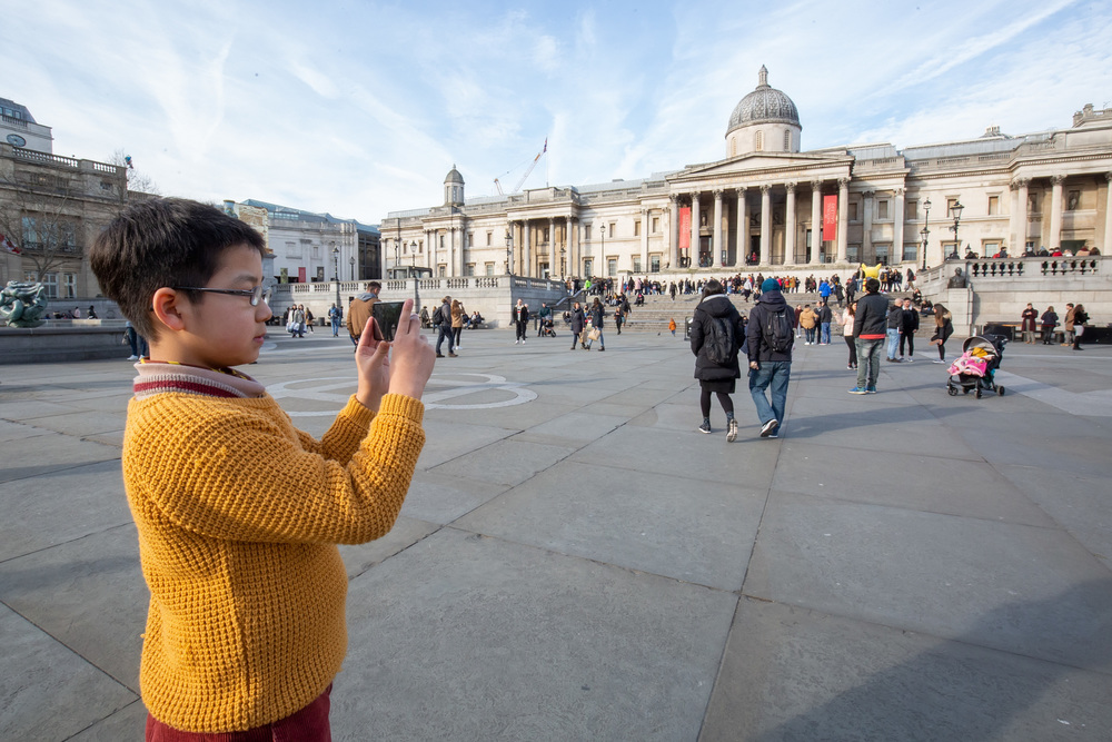 Schoolboy takes photograph in Trafalgar Square